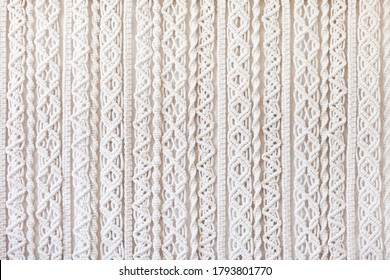 Close-up of hand made macrame texture pattern. ECO friendly modern knitting DIY natural decoration concept  in the interior. Flat lay. Handmade macrame 100% cotton. Female hobby.