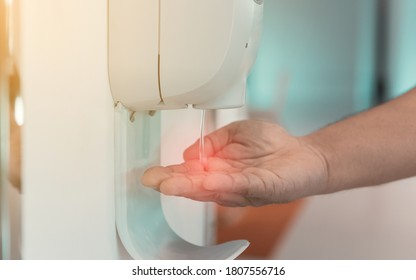 close-up hand male under automatic alcohol gel dispenser for cleaning hand and clear bacteria for stop Covid 19 virus outbreak. Protection against the virus, Covid-19, corona virus 2019