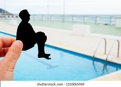 closeup of the hand of a man with a black paper cutout in the shape of a man throwing himself into a swimming pool