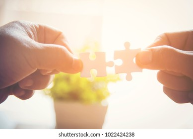 Closeup hand of man connecting jigsaw puzzle with sunlight effect, Business solutions, success and strategy concept