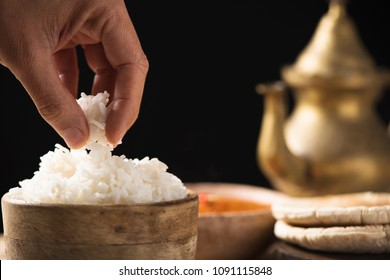 closeup of the hand of a man having some cooked rice from a bowl placed on an off-white wooden table, next to a bowl with a chicken korma curry, some chapatti and a golden teapot in the background