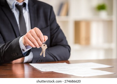 Close-up of hand of man is holding a key from a new apartment.
