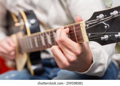 Closeup hand of man playing electric guitar. Selective focus on hand