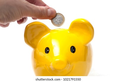 closeup of hand of man putting euro coin under yellow piggy bank on white background