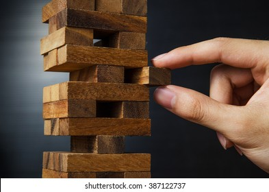 Closeup hand man take one block on The tower from wooden blocks, dark tone.