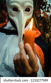 Closeup hand of a man in white shirt and black cloak wearing plague doctor mask holding an orange burning candle, toned image (focus on the mask). Happy Halloween night. Trick or treat