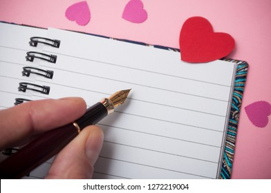 closeup of hand of man writing with vintage pen on spirales note book with paper hearts on pink background