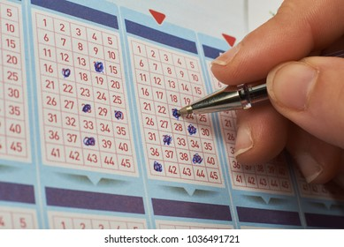 Closeup of hand marking number on lottery ticket with pen.