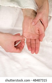 a closeup of a hand of a mature natural woman having a hand reflex zone massage at the thenar and at her little finger