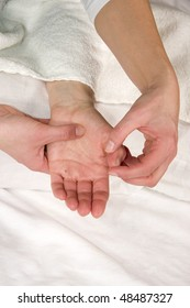 a closeup of a hand of a mature natural woman having a hand reflex zone massage at the thenar and at her thumb