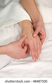 a closeup of a hand of a mature natural woman having a hand reflex zone massage at the back of her hand