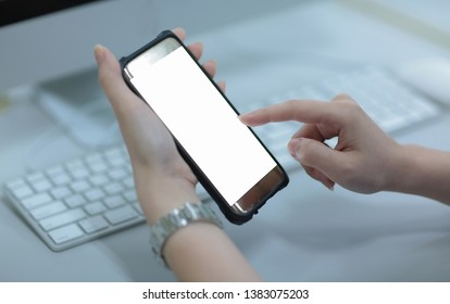 closeup of the hand with the mobile phone closeup on  white screen  and computer