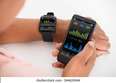 Close-up Of Hand With Mobile And Smartwatch Showing Heartbeat Rate