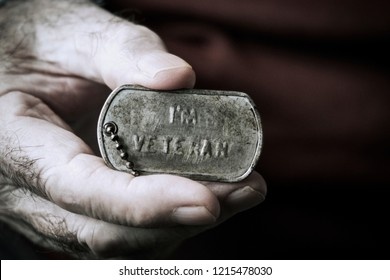 closeup the hand of an old caucasian man showing a dog tag with the text I am veteran engraved in it
