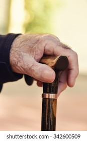 closeup of the hand of an old caucasian man with a walking stick, outdoors