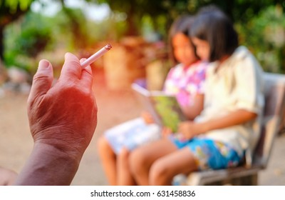 Close-up hand of one man sits smoking in a public place on blur background. It's dangerous for people around. (world no tobacco day)