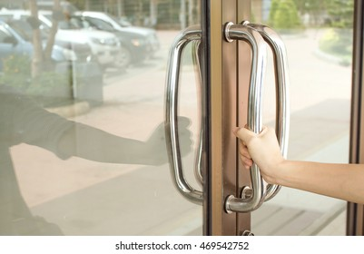 Close-up of hand open Aluminum glass door holding handle.