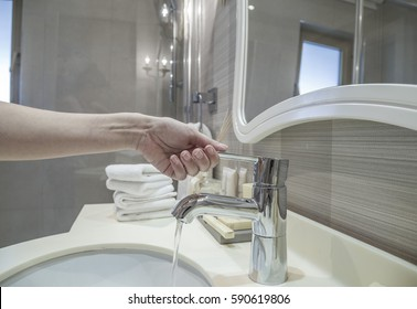 closeup of a hand opening water tap in bathroom