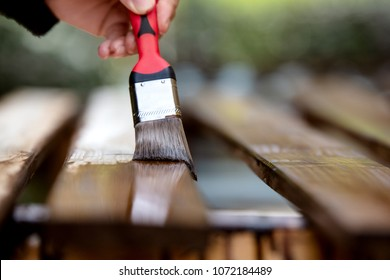 Close-up of a hand with paintbrush, wooden boards are varnished or stained. Brushing boards with dark brown glaze for weather protection
