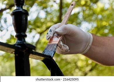 A closeup of a hand painting a railing black