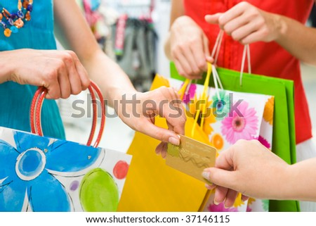 Close-up of woman?s hand passing over credit card to shop assistant on background of another female