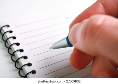 Close-up of hand with a pen on notepad