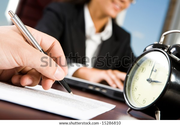 Close-up of maleâ??s hand with pen over document on background of working woman