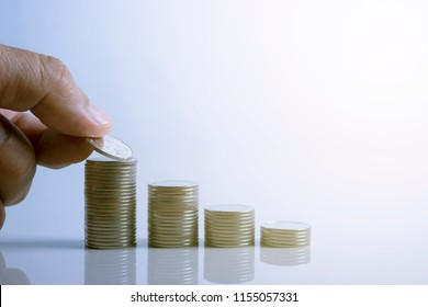 closeup hand of person holding a coin to put on the pile of coins on desk in soft  background.