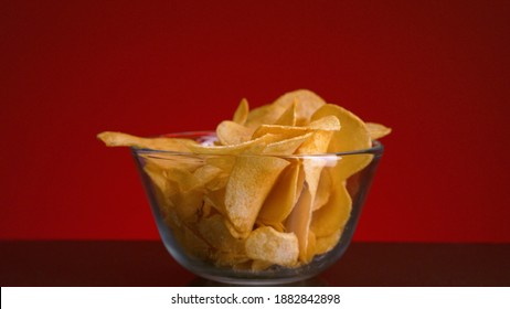 Close-up of hand picking up chips. Stock footage. Person takes one potato chip from bowl on isolated background. Chips in transparent bowl on red background. Junk food and snacks