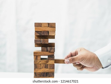 Close-up of hand placing wooden block on tower. Risk concept.
