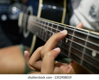 closeup of hand playing the guitar.