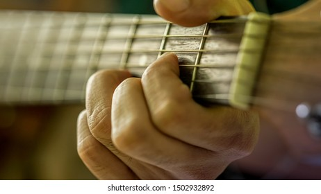 Closeup of hand playing A minor chord on guitar, isolated