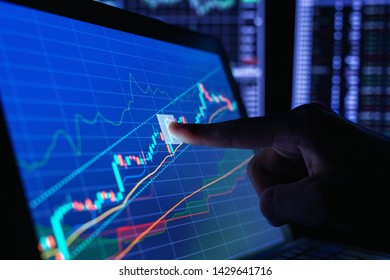 Closeup hand pointing finger and touching blue color monitor to analyze stock market graph