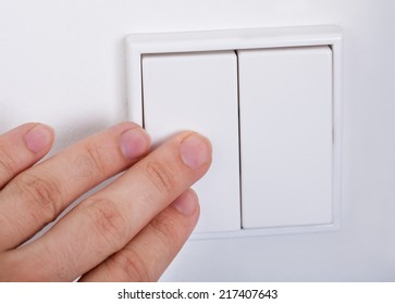 Close-up Of Hand Presses The Light Switch On The Wall