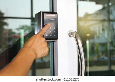 Close-up hand pressing keyword to lock and unlock door - Door access control keypad with keycard reader