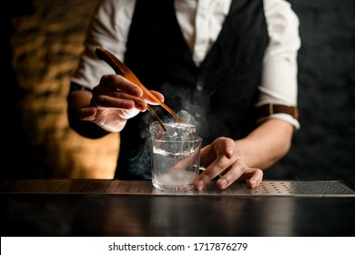 close-up hand of professional bartender which holds tweezers with ice cube and puts it in steaming glass