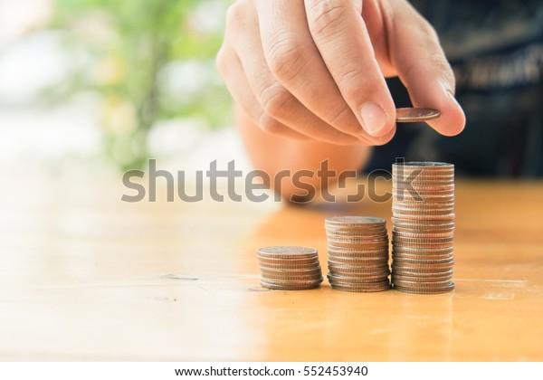 Closeup of hand put Coins to stack of coins,Concept Saving money. Saving money back car