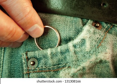 Closeup of a man�´s hand put in or taking out a wedding ring in the worn jeans pocket. Concept of infidelity or asking in marriage.