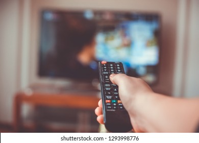 Close-up of hand with the remote control television and presses the button