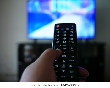 closeup of hand with the remote control television and presses the button.