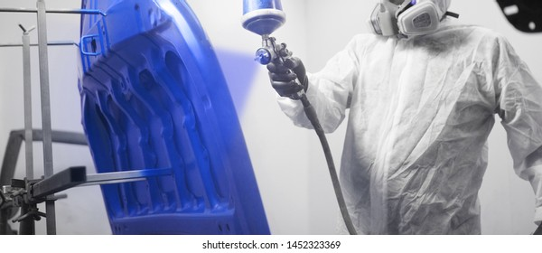 Close-up, hand of repairman painting car body elements in the paint chamber.