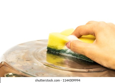 close-up of hand scrubbing cooking pot by scouring pad (yellow sponge)