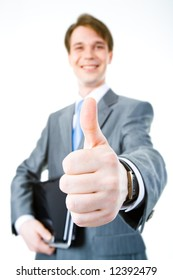 Close-up of businessman's hand showing thumb up on the background of male with laptop