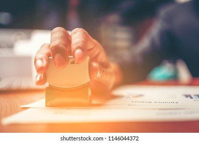 Close-up hand stamping of businessman for signing approval on documents , business concept