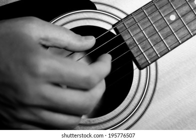 Close-up of a hand strumming a guitar in b&w