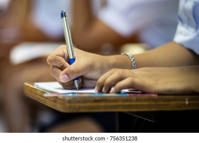 Closeup to hand of student  holding pen and taking exam in classroom with stress for education test.