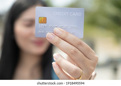 Closeup hand takes of credit card for financial transactions and blurred background women