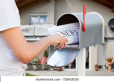 Close-up Of Hand Taking Newspaper From Mailbox In Front Of Their House
