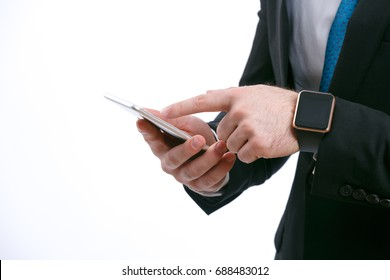 Close-up - hand of unknown businessman working with smart phone and wearing black smart watch on white isolated background