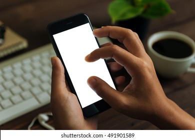 closeup hand use phone showing white screen on work desk, blank phone screen with clipping path easy for adjust app screen